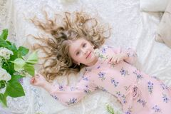 Cute little girl with blond hair in a beautiful dress in a spring studio with lilac. Flowers stock photography