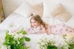 Cute little girl with blond hair in a beautiful dress in a spring studio with lilac. Flowers royalty free stock photo