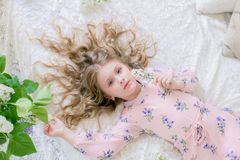 Cute little girl with blond hair in a beautiful dress in a spring studio with lilac. Flowers stock photo