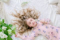 Cute little girl with blond hair in a beautiful dress in a spring studio with lilac. Flowers stock image