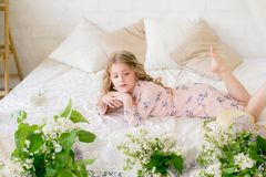 Cute little girl with blond hair in a beautiful dress in a spring studio with lilac. Flowers royalty free stock image