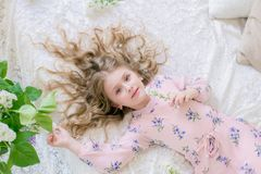 Cute little girl with blond hair in a beautiful dress in a spring studio with lilac. Flowers stock photos
