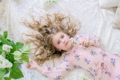 Cute little girl with blond hair in a beautiful dress in a spring studio with lilac. Flowers royalty free stock images