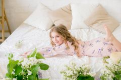 Cute little girl with blond hair in a beautiful dress in a spring studio with lilac. Flowers stock images