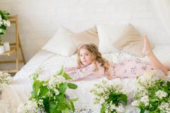 Cute little girl with blond hair in a beautiful dress in a spring studio with lilac. Flowers royalty free stock photos