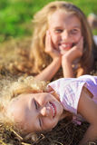 Cute little girl with blond hair laying in hay. Heap on green lawn Stock Photos