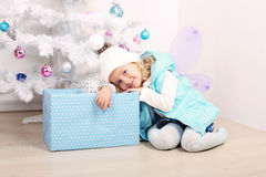 Cute little girl with blond hair posing beside a Christmas tree Stock Photo