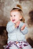 Cute little girl with blond hair sitting on chair and laughing. Cute little girl with blond hair sitting on chair, laughing and clapping her hands. Studio Stock Photos