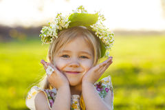 Cute little girl with blond hair in a wreath of lily of the vall Stock Photography
