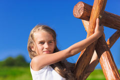 Cute little girl with blond long hair. Playing on wooden chain swing Stock Photo