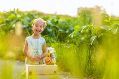Cute little girl with blonde hair drinking lemonade outdoor. Detox fruit infused flavored water, cocktail in a beverage dispenser royalty free stock photos