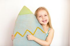 Cute little girl with blonde hair holding surfboard on white background royalty free stock image