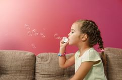 Cute little girl blowing bubbles indoors,. Copy space , red wall background stock images