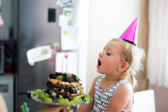 Cute little girl blowing candles on her birthday cake Stock Images