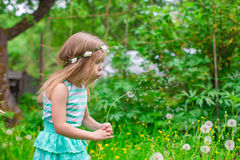 Cute little girl blowing a dandelion in the garden Royalty Free Stock Photo