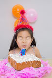 Cute little girl blowing her birthday cake Royalty Free Stock Photography