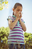 Cute little girl blowing her nose in park Royalty Free Stock Photography
