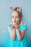 Cute little girl blowing magical dust. Royalty Free Stock Photo
