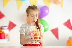Cute little girl blowing out candles on birthday cake Royalty Free Stock Image