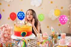 Cute little girl blowing out candles on her birthday Royalty Free Stock Image