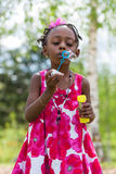 Cute little girl blowing soap bubbles Royalty Free Stock Images