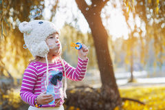 Cute little girl is blowing a soap bubbles Stock Photo