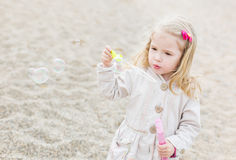 Cute little girl blowing soap bubbles Stock Photography