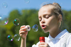 Cute little girl blowing soap bubbles Stock Photos