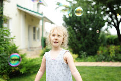 Cute little girl is blowing a soap bubbles and having fun Stock Images