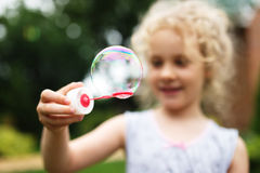 Cute little girl is blowing a soap bubbles and having fun Stock Image