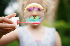 Cute little girl is blowing a soap bubbles and having fun Royalty Free Stock Photography