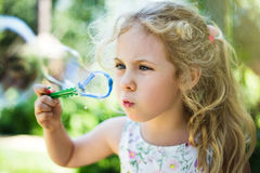 Cute little girl is blowing a soap bubbles and having fun Stock Photography