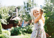 Cute little girl is blowing a soap bubbles and having fun Stock Photos
