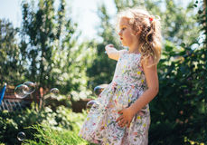 Cute little girl is blowing a soap bubbles and having fun Royalty Free Stock Photos