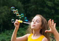 Cute Little Girl blowing soap bubbles outdoor at summer day - ha Stock Photos