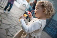 Cute little girl blowing soap bubbles Stock Images