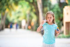 Adorable little girl making soap bubbles during summer vacation royalty free stock images