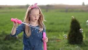 Cute little girl blowing soap bubbles outdoors stock footage