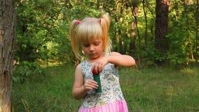 Cute little girl blowing soap bubbles in park stock footage