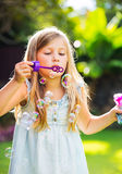 Cute little girl blowing soap bubbles Royalty Free Stock Photos