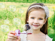 Cute little girl is blowing a soap bubbles Stock Images