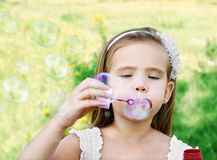 Cute little girl is blowing a soap bubbles Stock Image