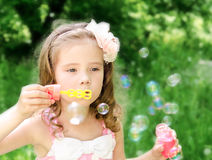 Cute little girl is blowing a soap bubbles Royalty Free Stock Photo