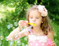 Cute little girl is blowing a soap bubbles Stock Photography