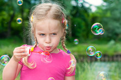 Cute little girl blowing soap bubbles Stock Photo
