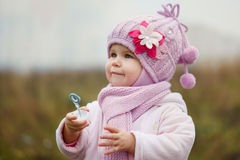 A cute little girl blows bubbles in autumn Stock Image