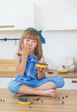 Cute little girl in blue dress eats a cake and licks her fingers Royalty Free Stock Photos