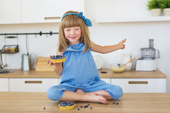 Cute little girl in blue dress sits on a table with a cake in a hand and closed eyes Royalty Free Stock Images