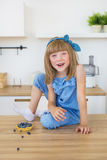 Cute little girl in blue dress sits on a table and and smiles Royalty Free Stock Photo