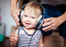 Cute little girl with blue eyes in the headphones, smiling Royalty Free Stock Images